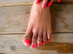 Black girl models her pretty pedicure in close up with pink polish